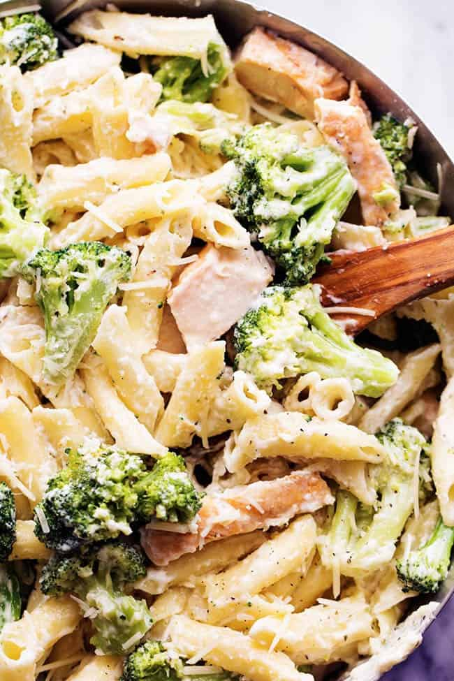 three cheese chicken broccoli alfredo in a pot with a wooden spoon.