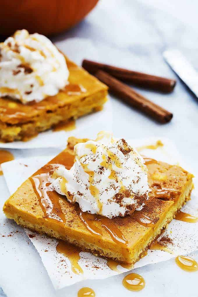pumpkin sheet cake topped with whipped cream and caramel sauce.