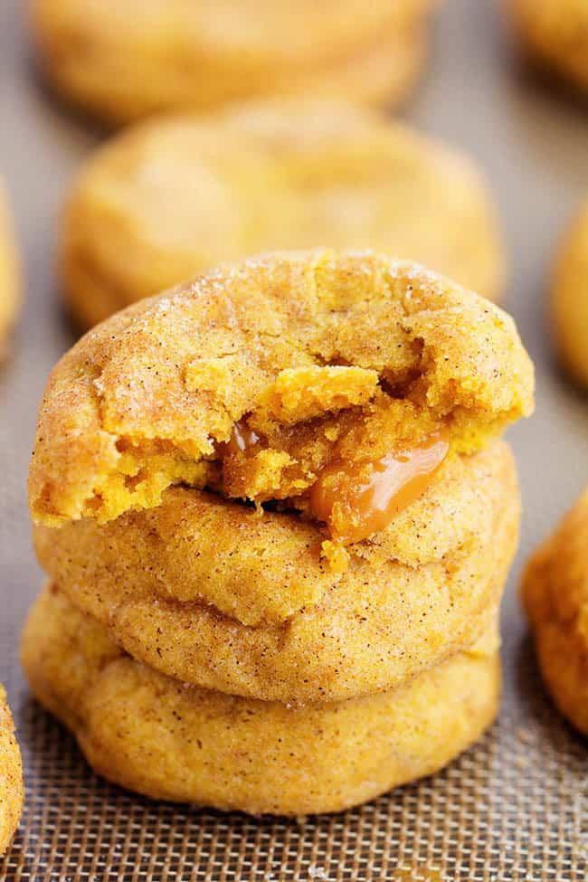 caramel pumpkin snickerdoodle cookies in a stack with the top cookie cut in half to show gooey inside.