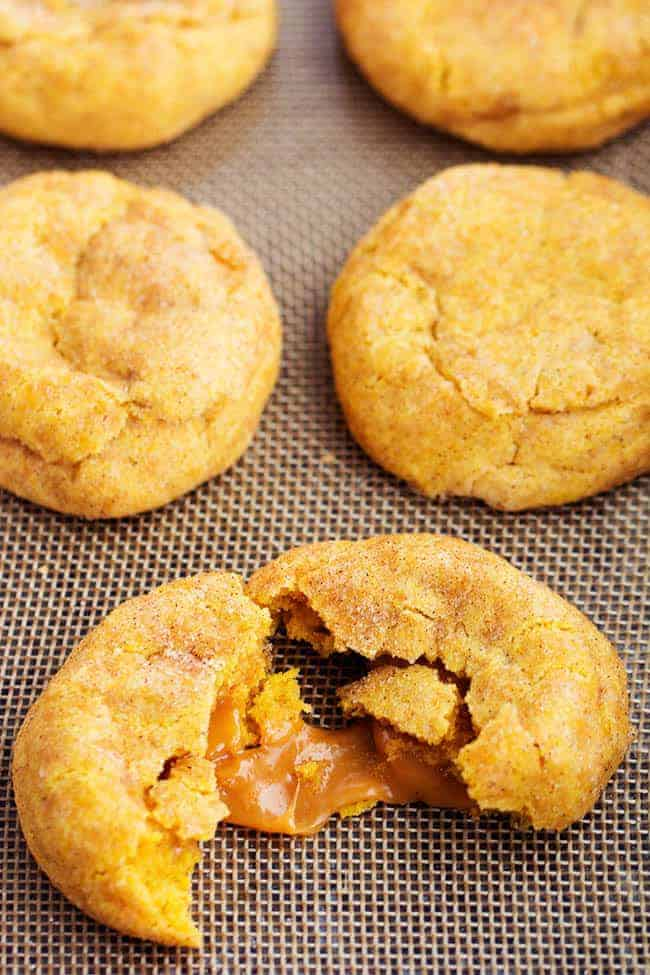 caramel pumpkin snickerdoodles with one torn into two to show the gooey inside.