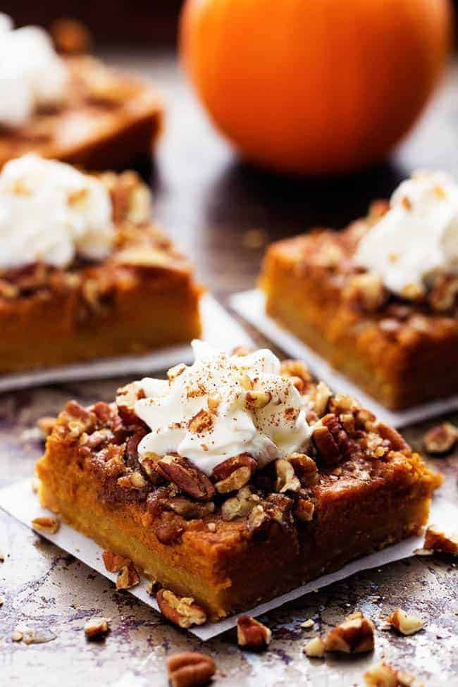 "Pumpkin pecan pie bars sliced into 2"" x 2"" Pieces on a parchment paper."