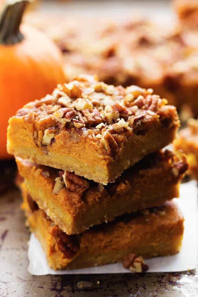 Three pumpkin pecan pie bars stacked on top of each other.