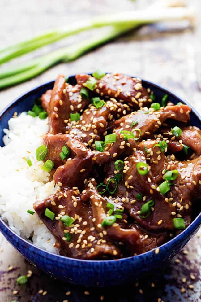 slow cooker korean beef with white rice in a blue bowl.