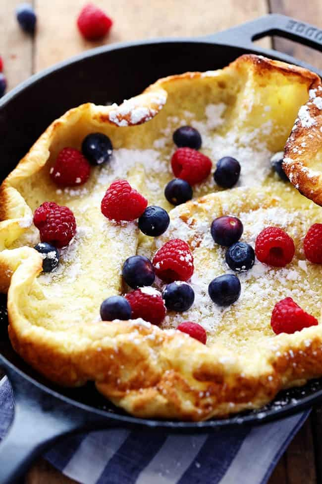 German pancakes with fresh berries over top with powdered sugar.