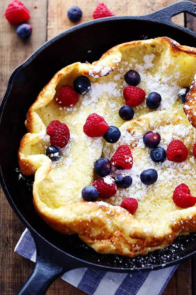 German pancake in a pan with fresh berries and powdered sugar.