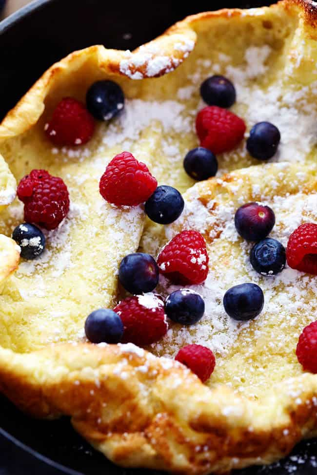 German oven pancake unclose photo with berries and powdered sugar.