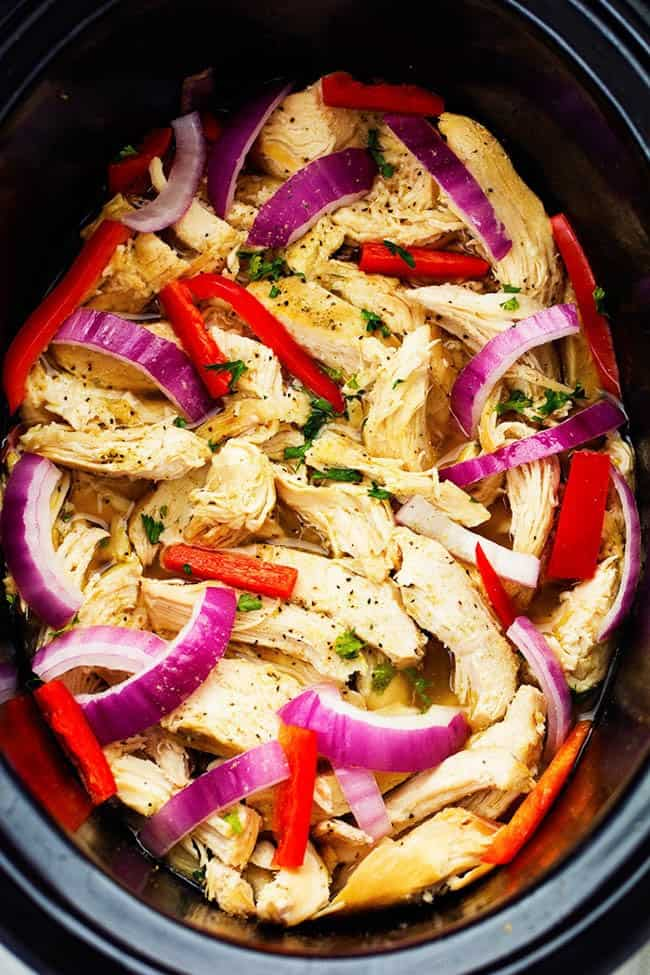 Chicken in a slow cooker with peppers and onions.