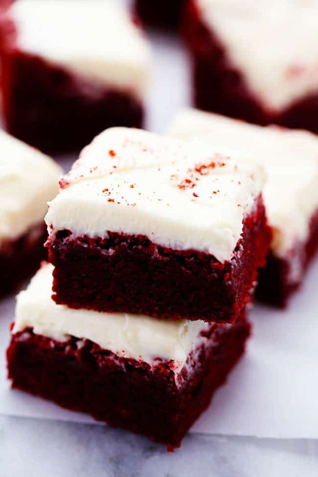 Red velvet brownies stacked on top of each other on the parchment paper.