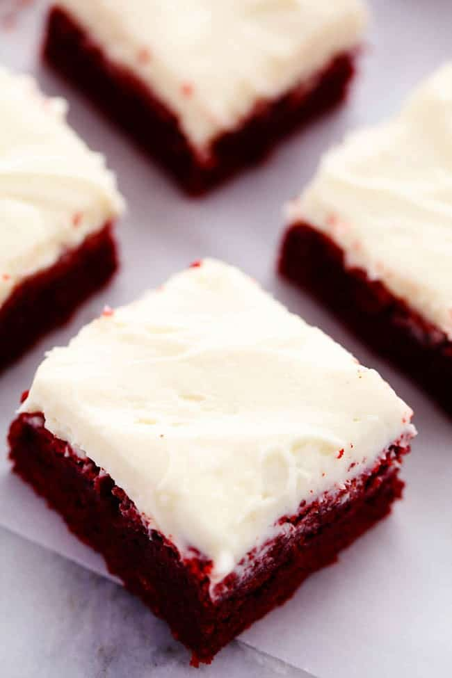 Red Velvet brownies separated cut into pieces on parchment paper.