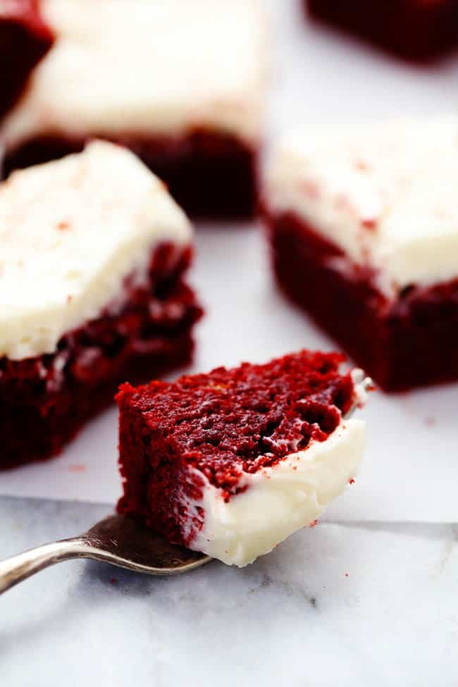 Red velvet brownies with a slice taken out using a fork.