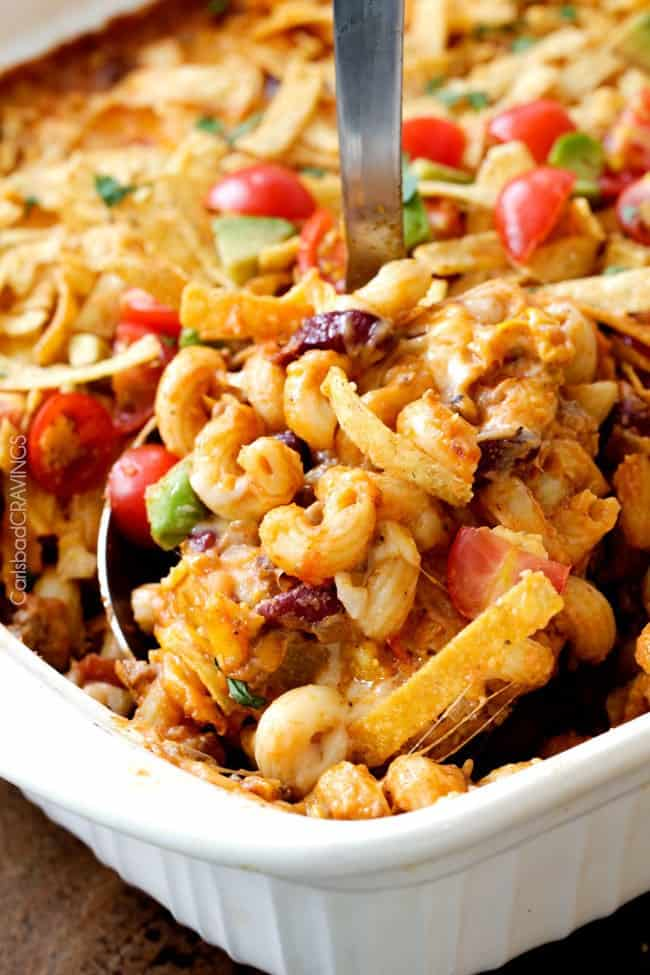 Taco chili pasta bake in a white casserole dish with a metal spoon removing some.