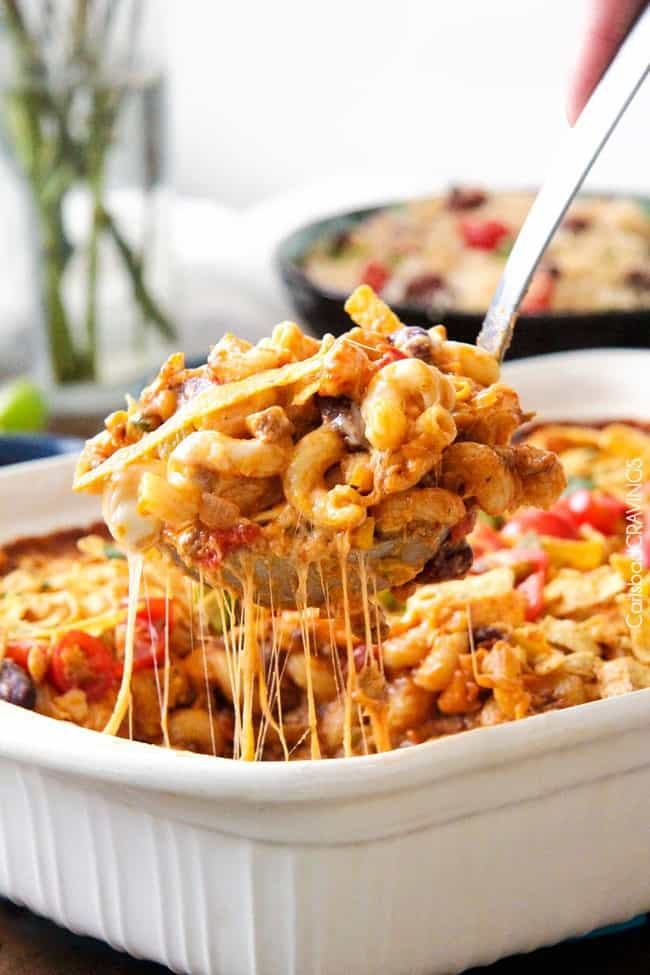 Taco Chili Pasta Bake in a white casserole dish with a spoon removing some.