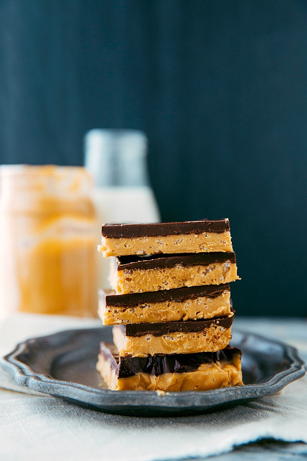 Crunchy peanut butter and chocolate bars stacked on top of one another on a gray plate.