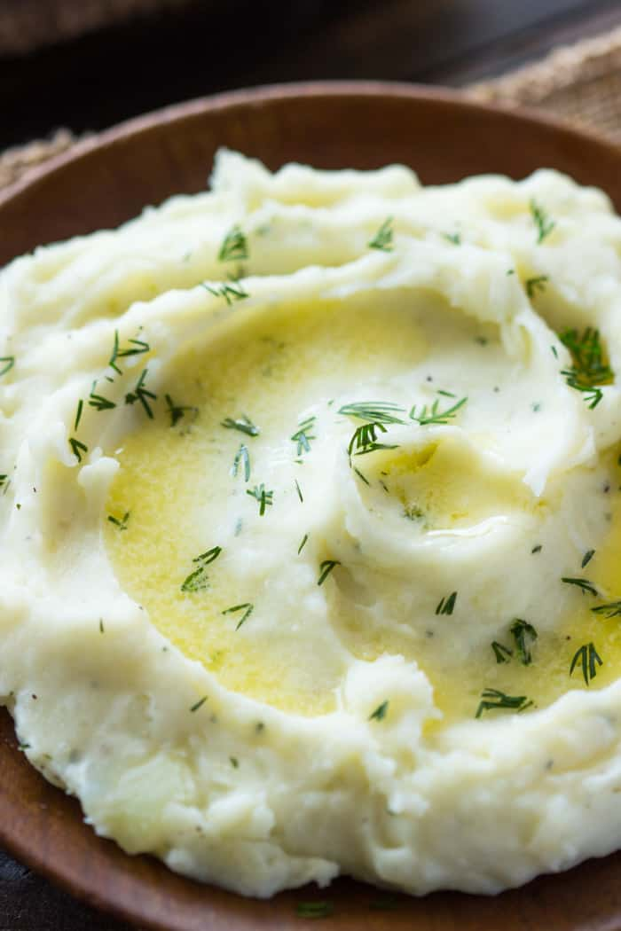 Close up photo of Slow Cooker Ranch Mashed Potatoes in a brown bowl.