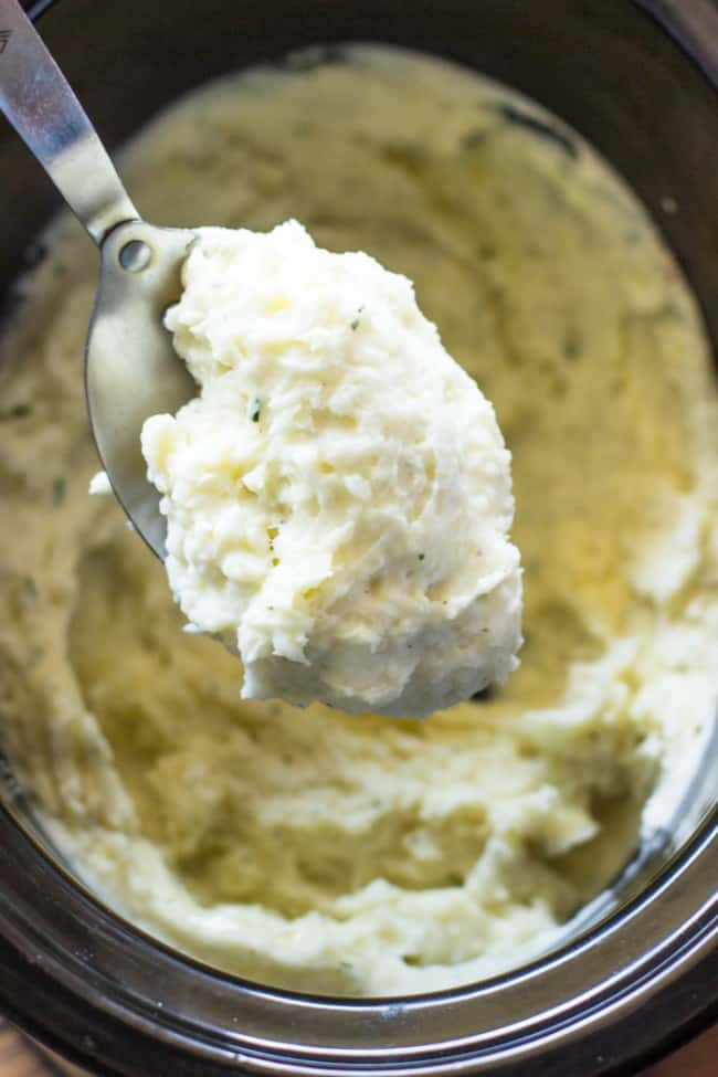 Close up photo of Slow Cooker Ranch Mashed Potatoes on a metal spoon.
