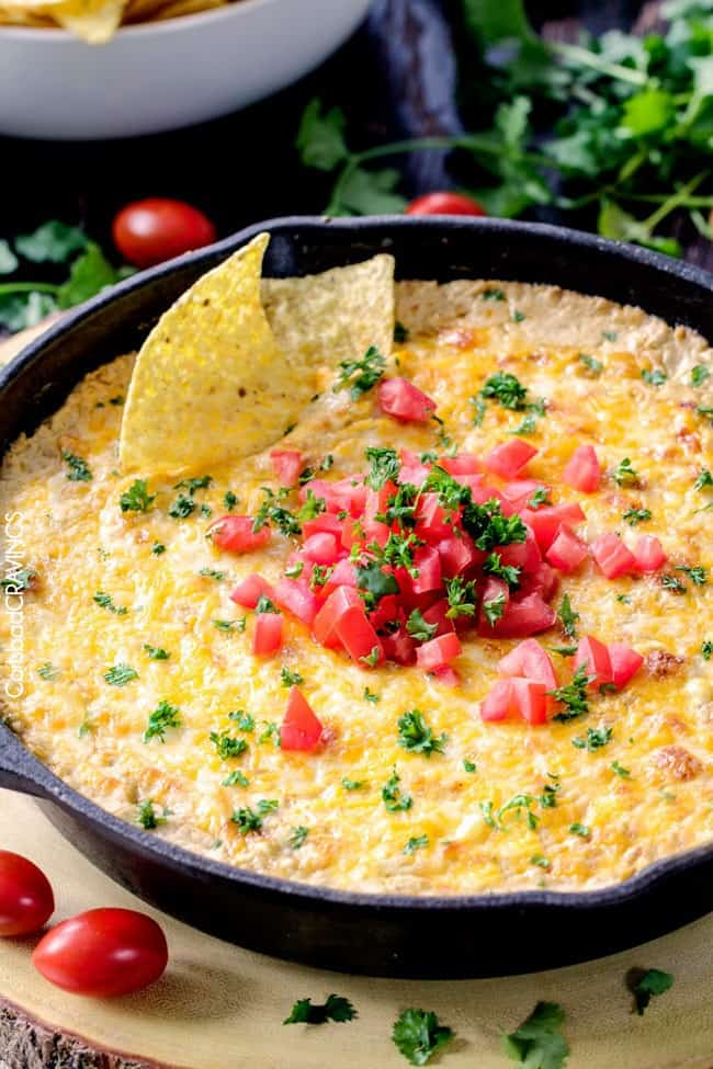 Queso verde corn dip in a large skillet with chips dipped into it.