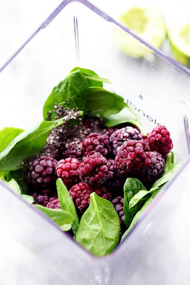 Fresh blackberries and spinach in a blender.