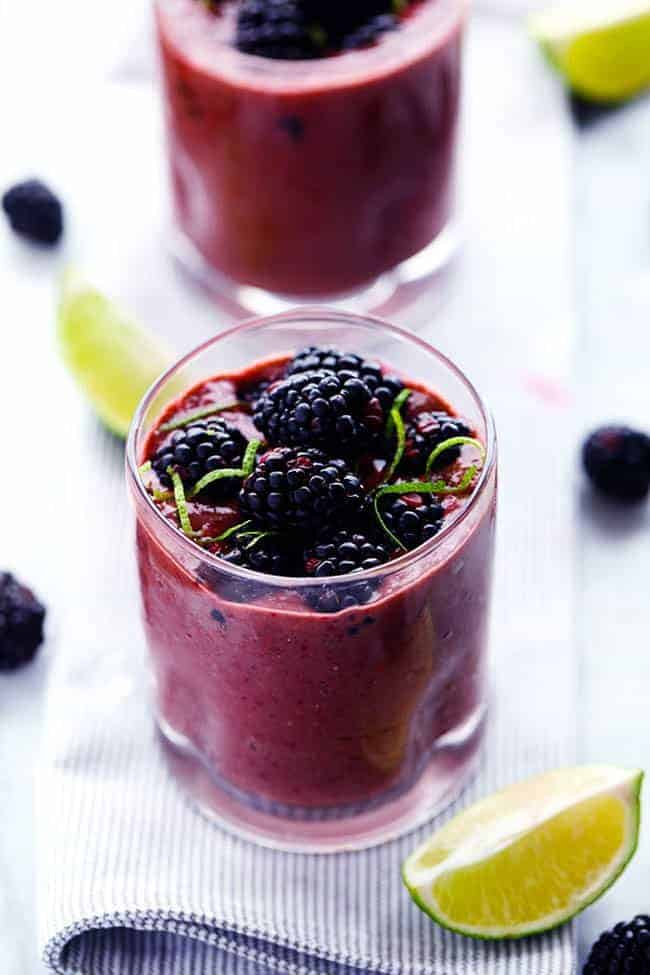 Blackberry lime smoothie in a clear glass with fresh cut limes on the side with fresh blackberries.s