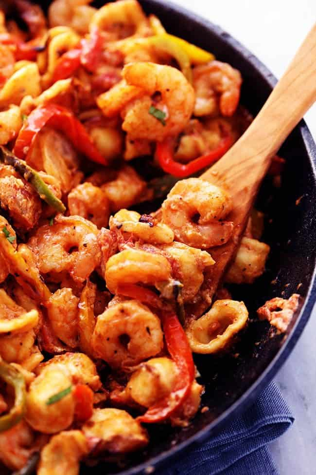 Creamy Shrimp Fajita Pasta Skillet with a wooden spoon mixing.