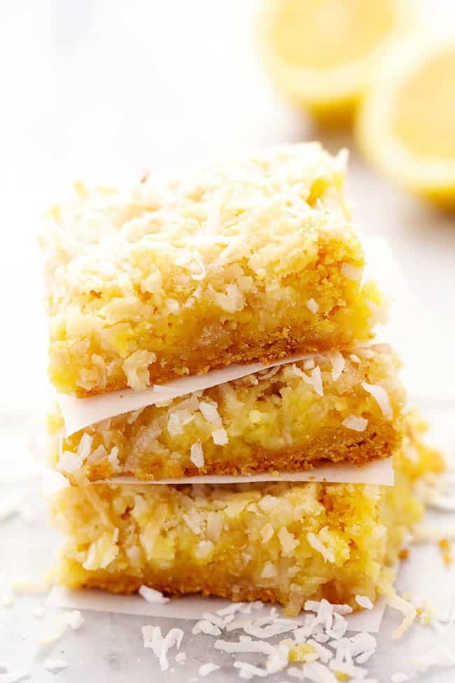 Lemon coconut butter bars stacked on top of one another.