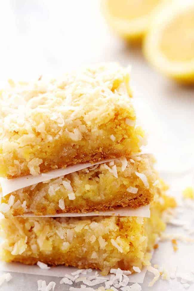 Lemon coconut butter bars stacked on top of each other with fresh cut lemons in the background.