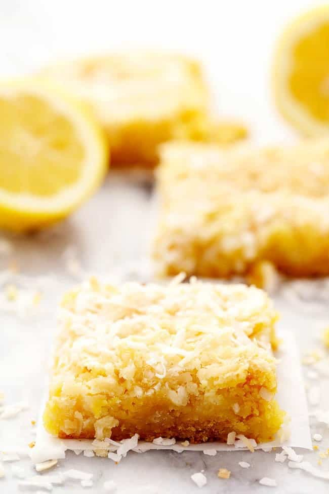 Lemon coconut butter bars with a fresh cut lemon in the background.
