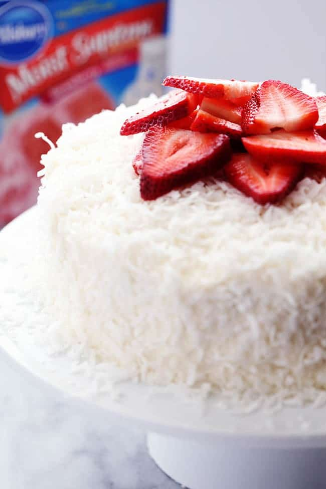 Strawberry Coconut Cream Cake with Coconut Cream Cheese Frosting with fresh cut strawberries on a white cake stand.