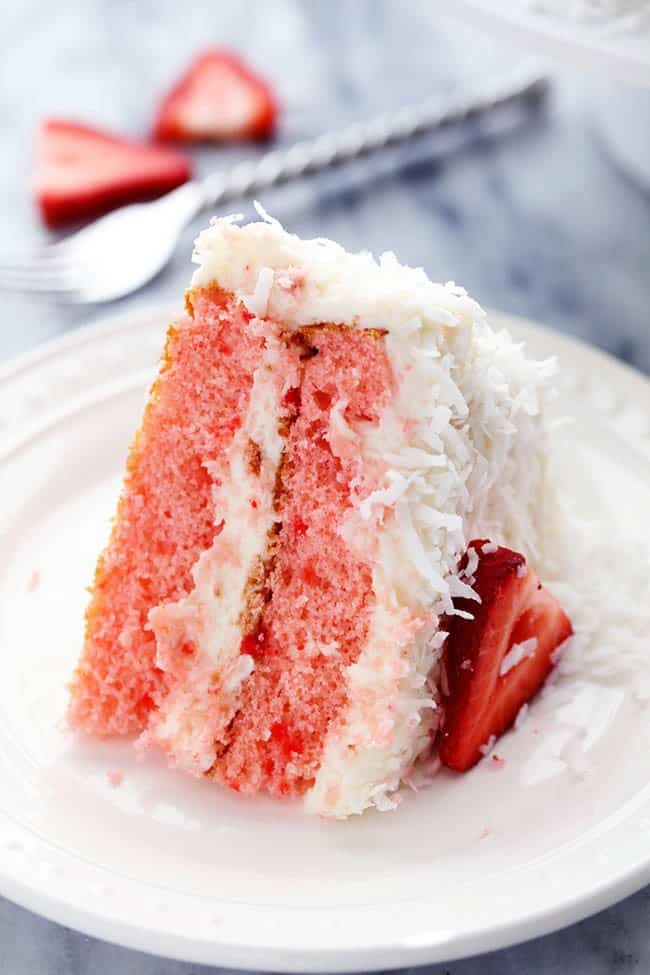 A slice of Strawberry Coconut Cream Cake with Coconut Cream Cheese Frosting on a white plate.