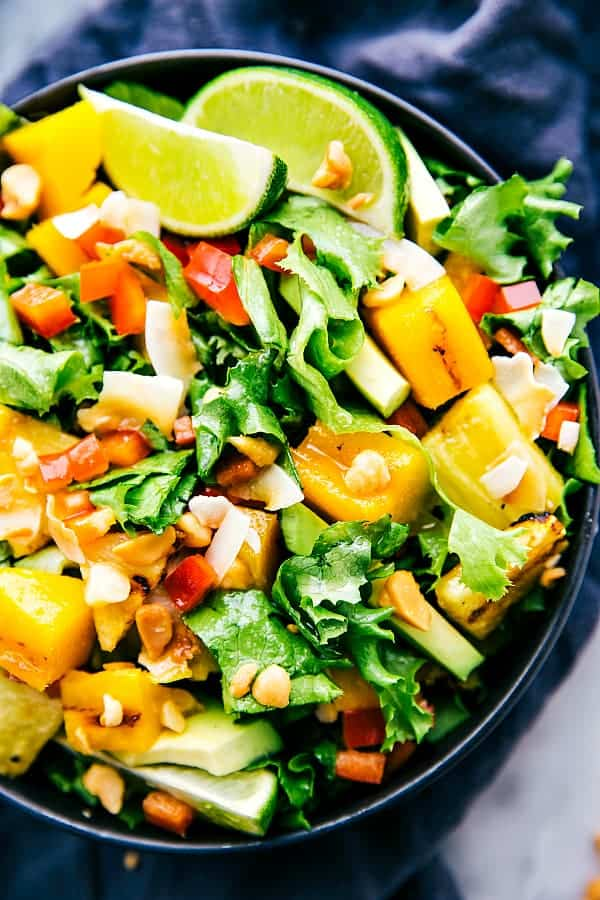 Grilled mango and pineapple salad in a large black bowl.