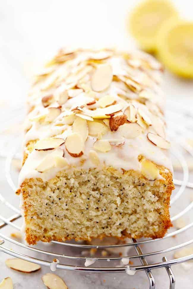Lemon Almond Poppyseed Quick Bread on a cooking rack with fresh lemons in the background.