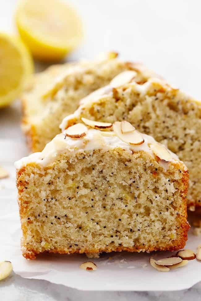 Slices of Lemon Almond Poppyseed Quick Bread on parchment paper.