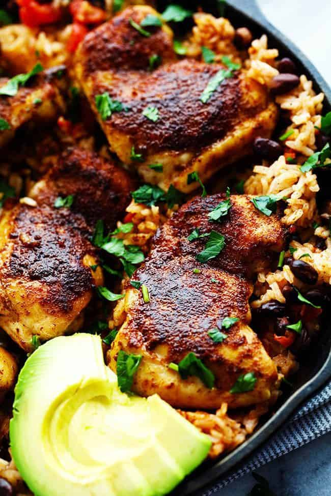 One Pan Southwest Blackened Cajun Chicken with Rice with fresh cut avocado in a large skillet.