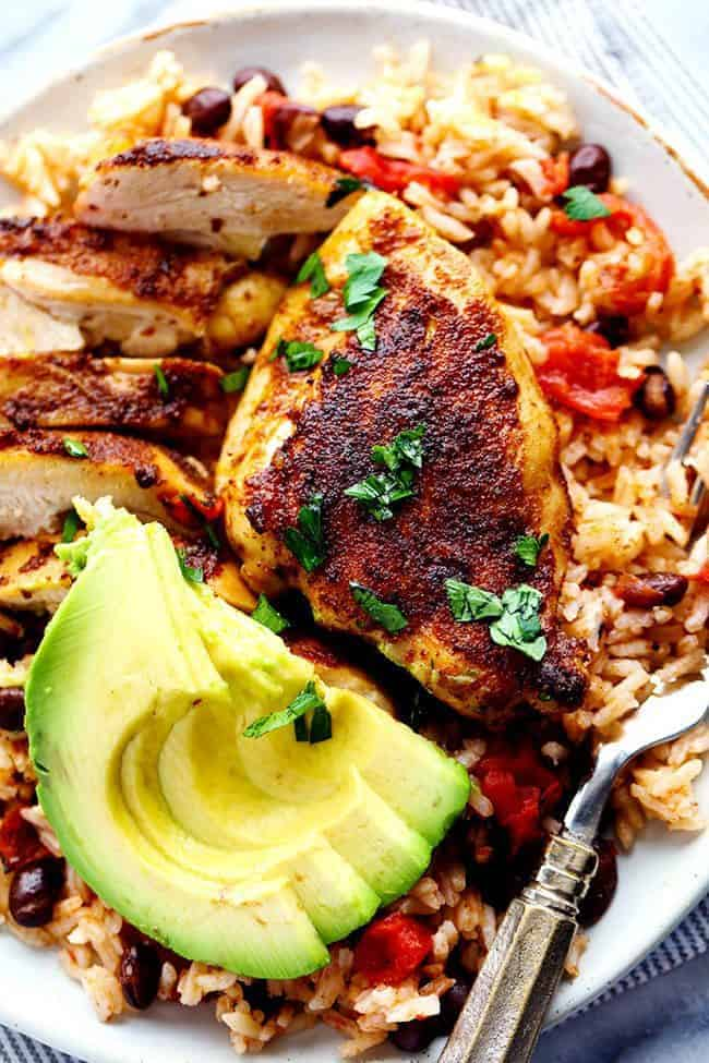 One Pan Southwest Blackened Cajun Chicken with Rice with fresh cut avocado on a white plate.