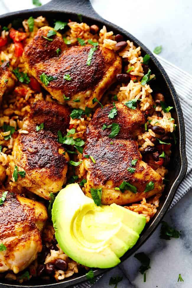 One Pan Southwest Blackened Cajun Chicken with Rice in a skillet with fresh cut avocado on the side.