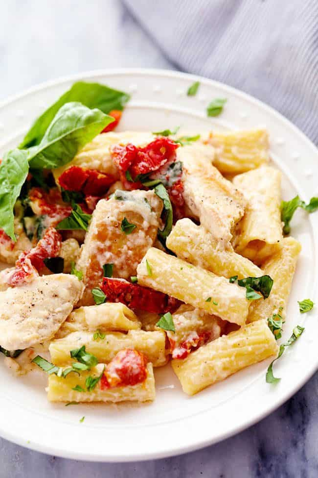 Mozzarella Chicken Pasta with Sun Dried Tomatoes on a white plate.