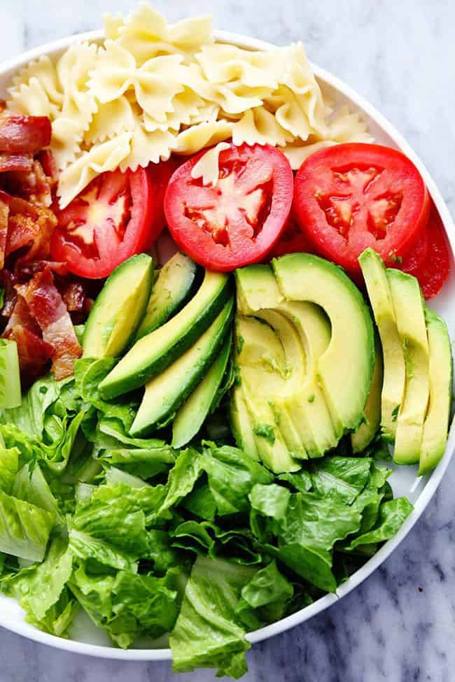 All of the ingredients for the BTL Avocado Pasta Salad in a large white bowl.