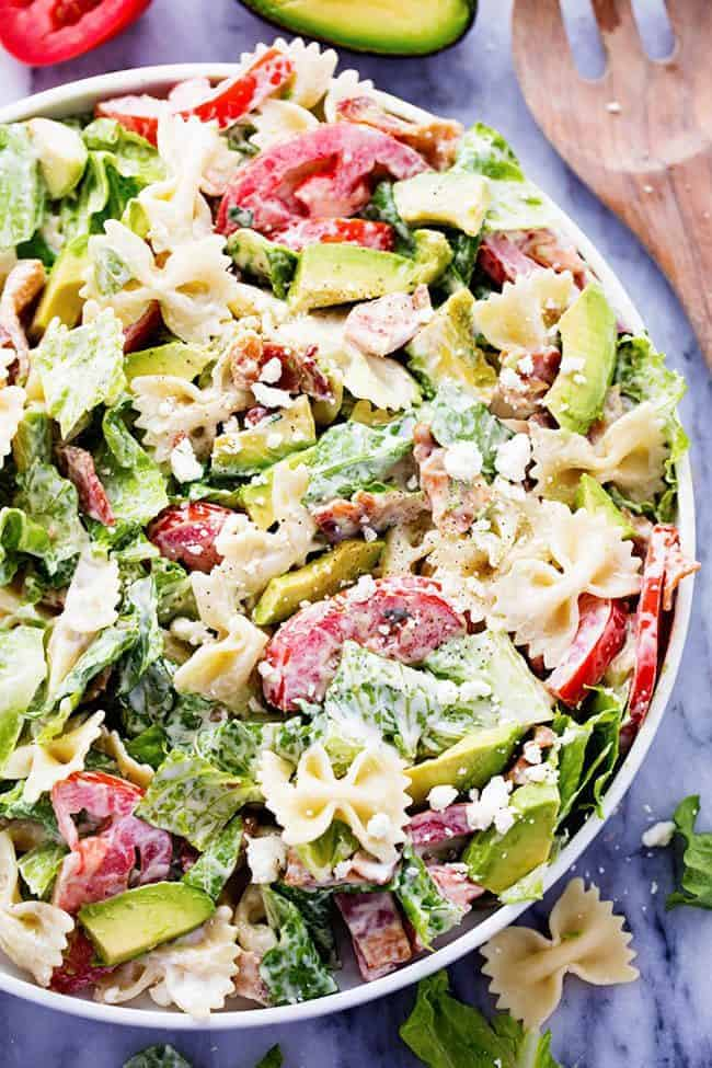 BLT Avocado Pasta Salad in a large bowl with a wooden spoon on the right side.