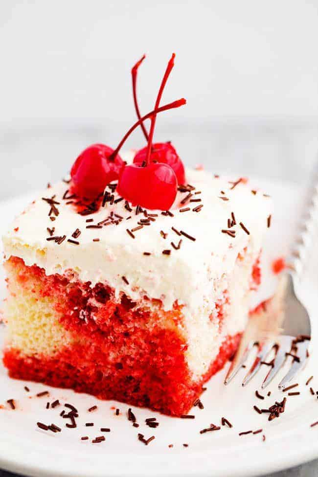 Cherry Jello Coke Poke Cake on a white plate with a metal fork with cherries on top.