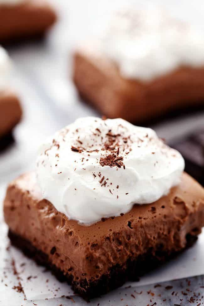 French Silk Pie Bars with whipped topping placed on white parchment paper.