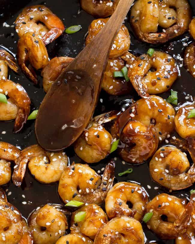 Hoisin Shrimp in a skillet with a wooden spoon.