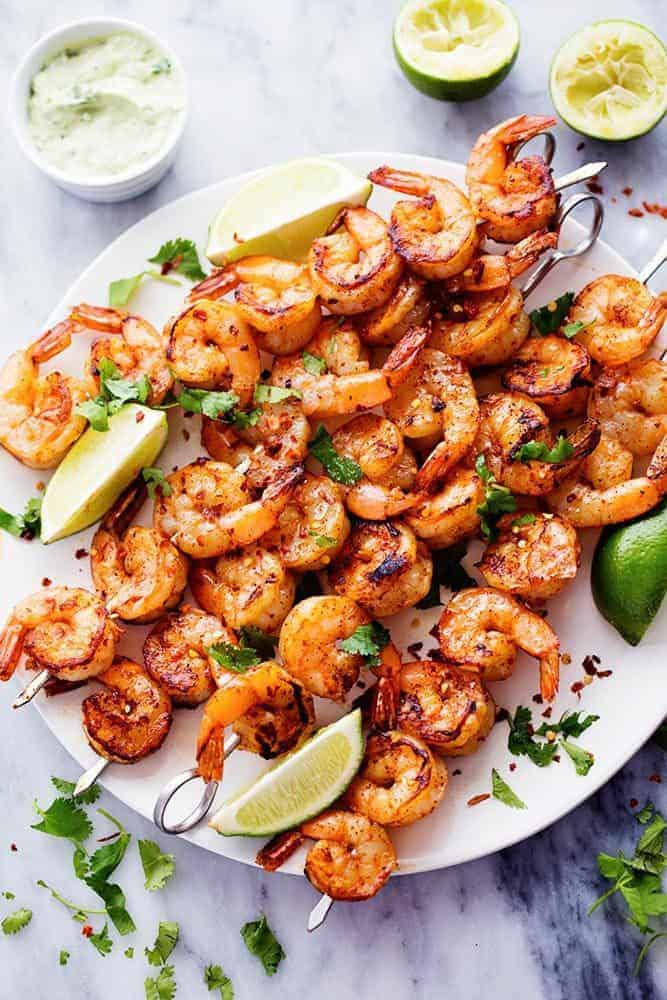 Grilled Spicy Lime Shrimp with Creamy Avocado Cilantro Sauce on skewers on a white plate with fresh limes on the side.