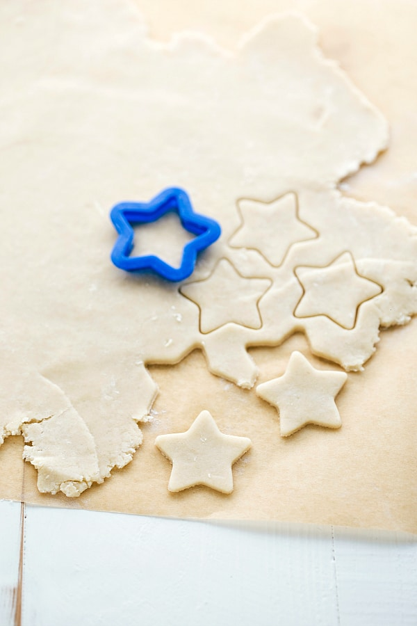 Uncooked pie crust being cut into star shapes for the top of the pie.