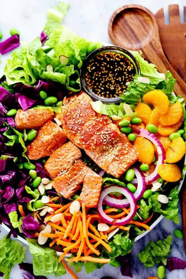 Overhead photo of Asian Pan Seared Salmon Salad in a large bowl with wooden tongs.