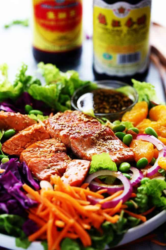 Asian Pan Seared Salmon Salad with two bottles of soy sauce on the side.