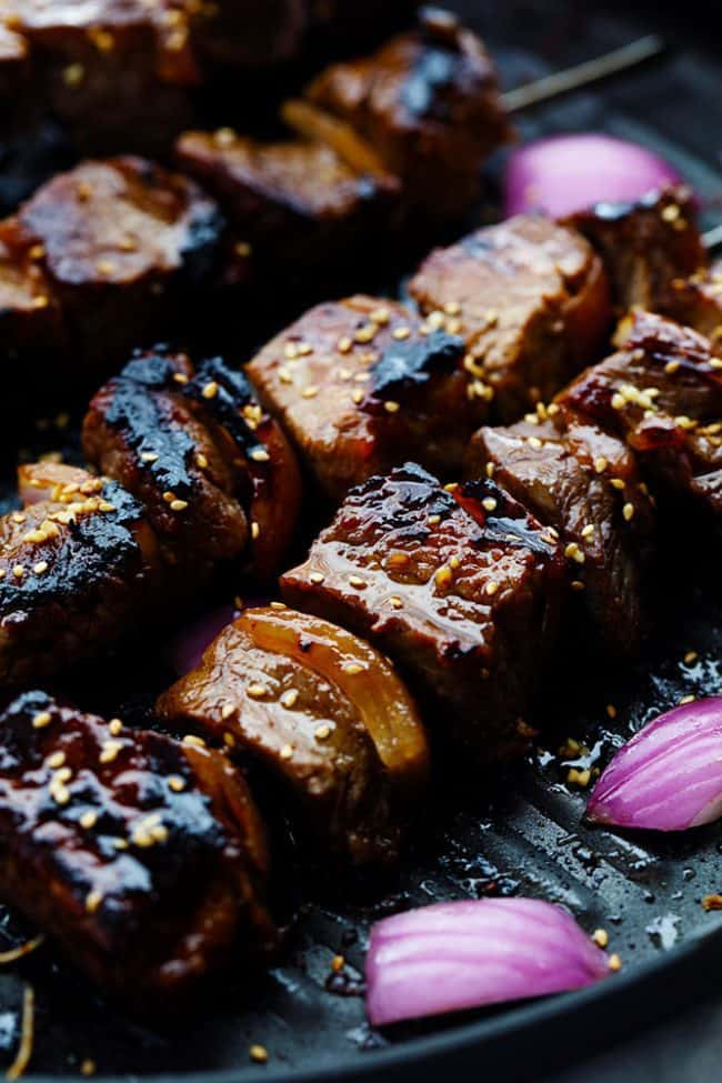 Steak skewers being grilled with onion on the side.