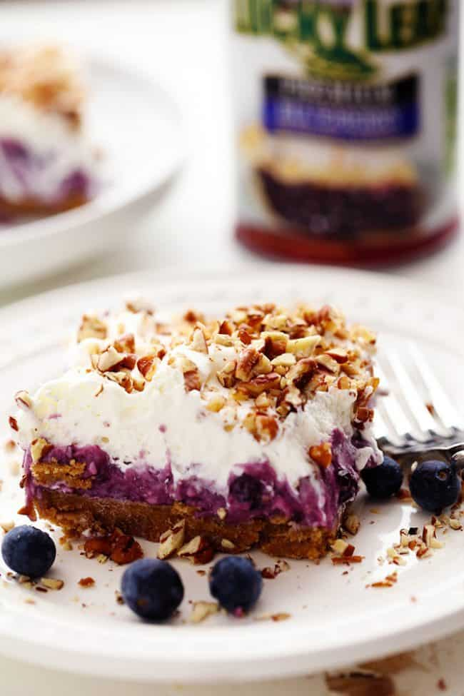 No Bake Creamy Blueberry Pecan Square on a white plate with a metal fork and fresh blueberries.