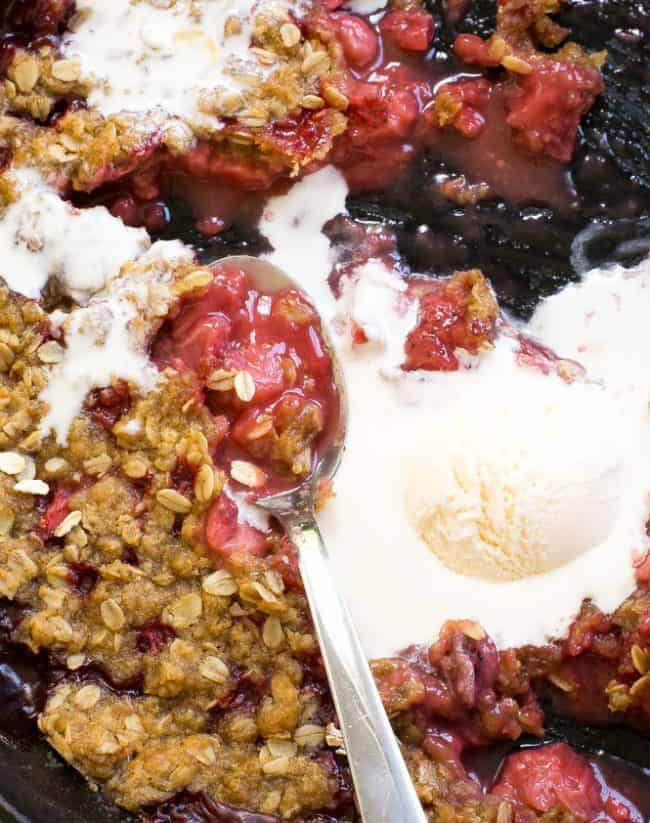 Strawberry Crisp in a bowl with a melting scoop of ice cream and a metal spoon.