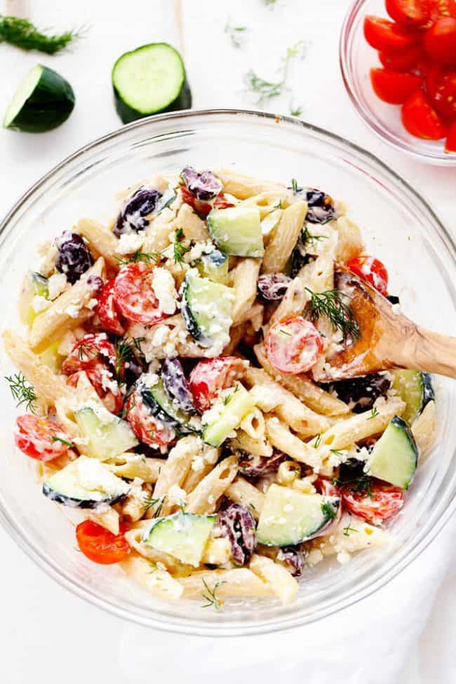 Overhead view of Greek Tzatziki Pasta Salad in a clear mixing bowl with a wooden spoon. There is a small clear bowl of tomatoes in the corner as well as a sliced cucumber.