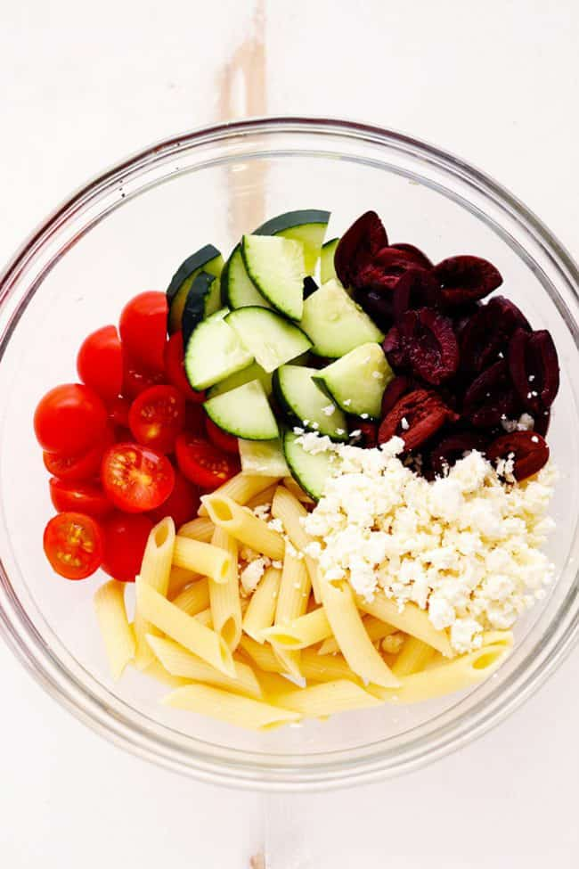Greek Tzatziki Pasta Salad ingredients in a glass bowl.
