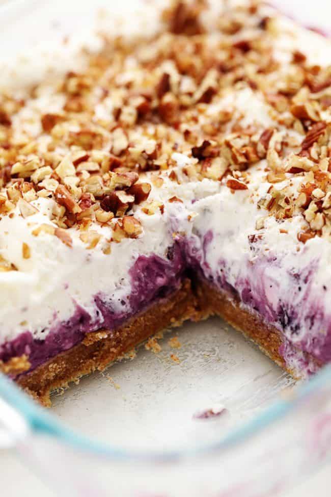 No Bake Creamy Blueberry Pecan Squares in a clear pan with one square removed.